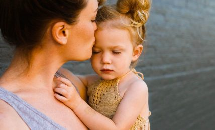 Mother kissing kid